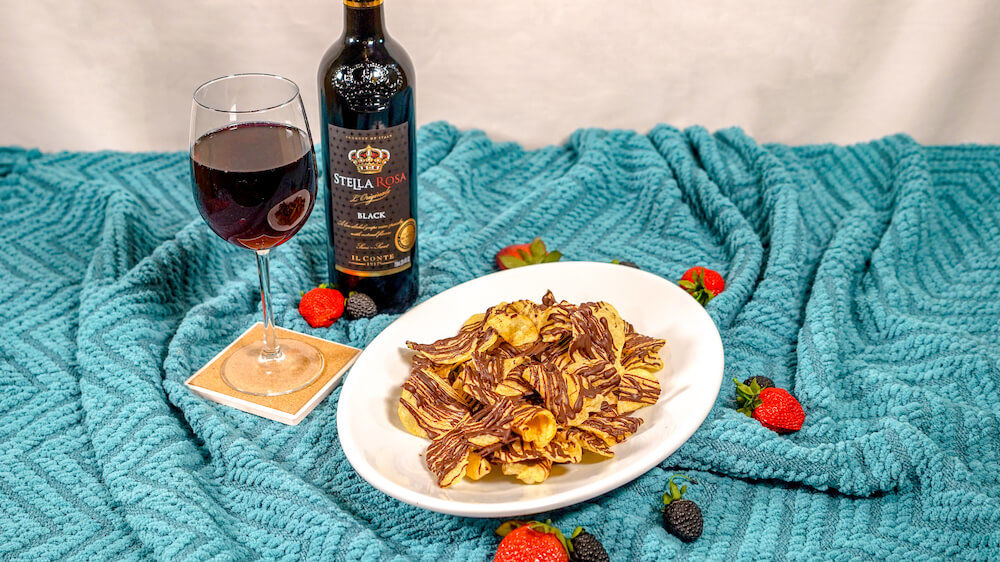 Stella Black bottle and full glass served next to white plate with chocolate covered potato chips on blue blanket.