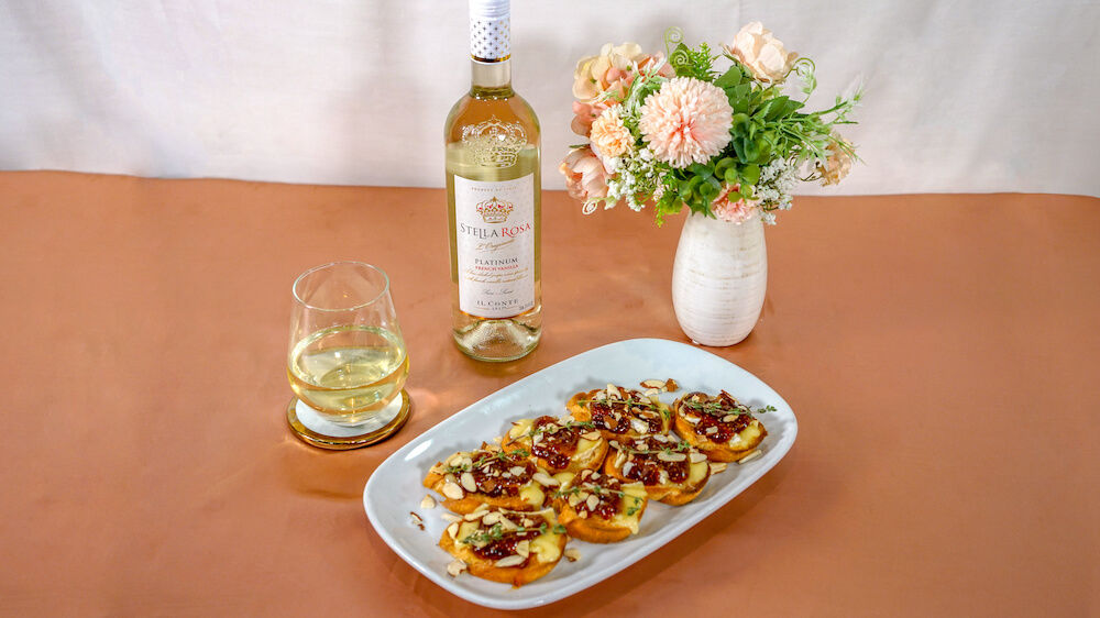Brie, fig jam toast served on white square plate over rose gold silk and served with bottle and glass of Platinum French Vanilla.
