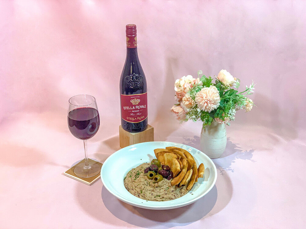 Stella Royale bottle placed next to olive hummus and pita chips served on a white plate with wine glass & vase on pink backdrop.