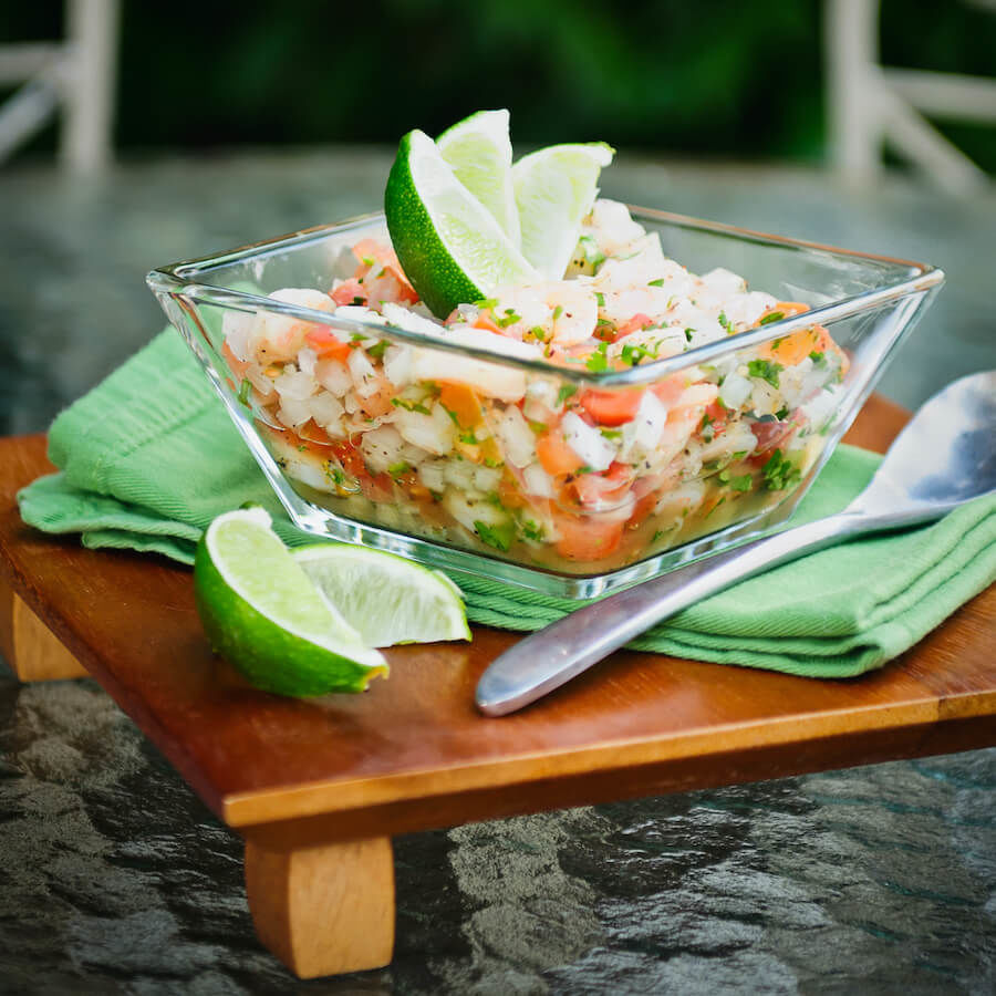 Grilled shrimp ceviche topped with limes served in a glass bowl.