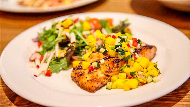 White fish topped with mango salsa served in a white plate over wood.