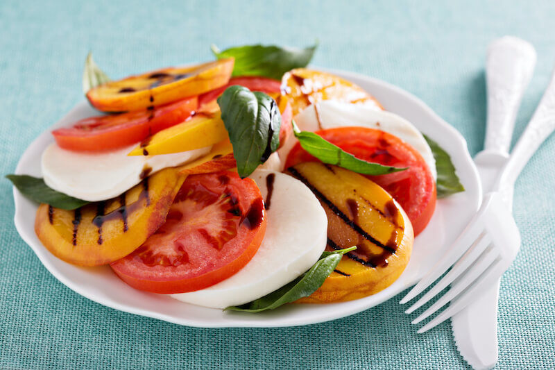 Grilled peaches, tomatoes and mozzarella caprese salad served on blue placemat.